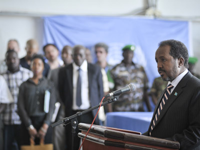 Somali President Hassan Sheikh Mohamoud speaks at the repatriation ceremony for three of the 15 people killed during the U.N. compound attach in Mogadishu