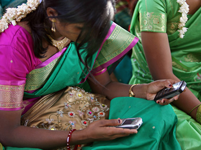 A young woman in Aurangabad, India using two mobile phones