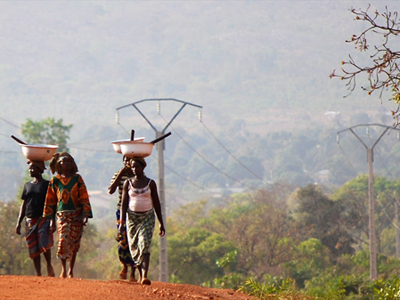 Women walk along the road in Benin